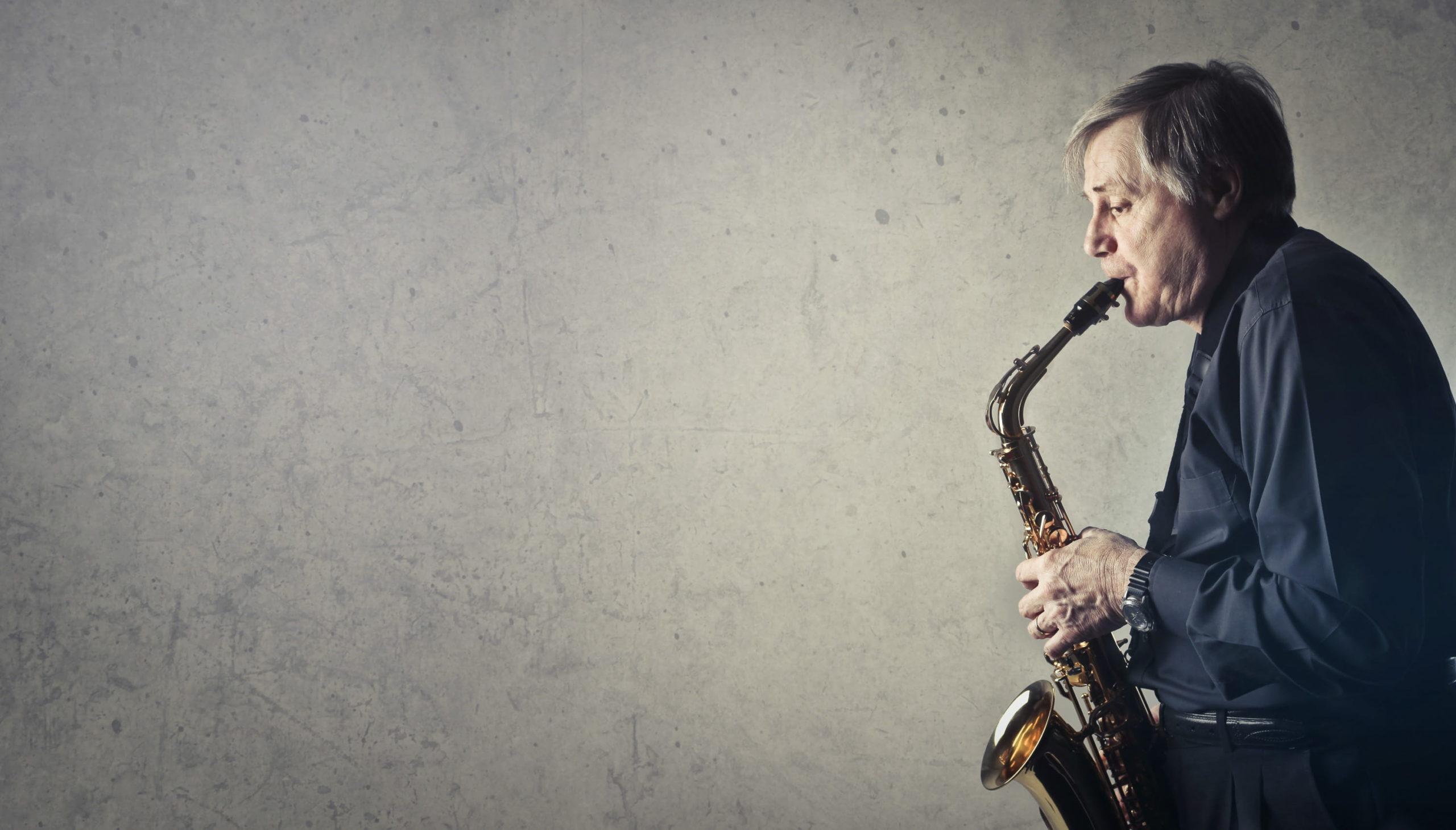Middle Aged Man Playing Saxophone on Gray Background Wall